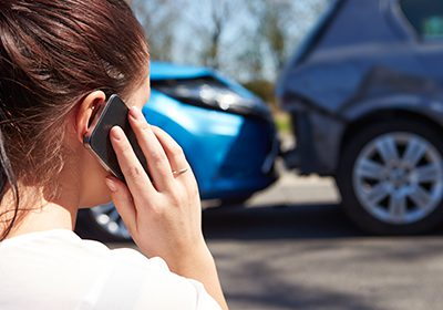Woman making call after car accident