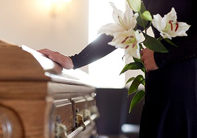 Wrongful death widow touching coffin